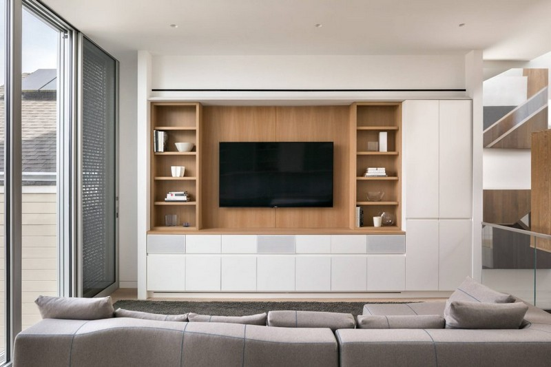 The living room is done with a sleek modern storage cabinet, a TV and a grey sofa