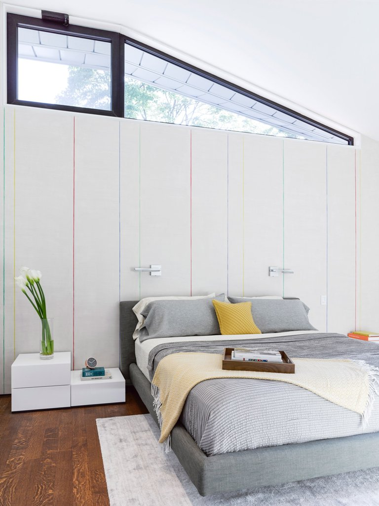 The master bedroom features an upholstered bed, an unusually shaped window and interesting wall cover