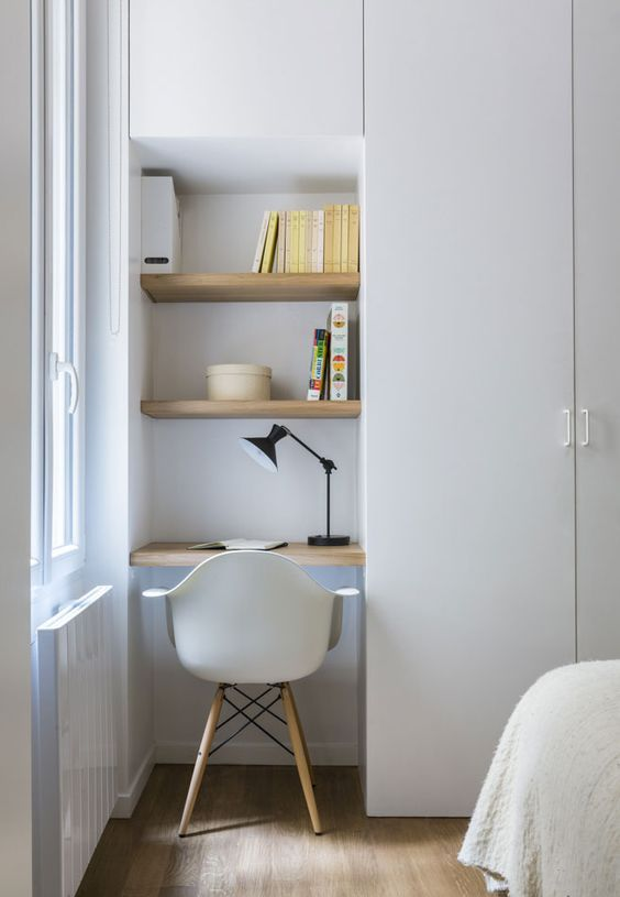 a very small and compact working space with built-in shelves by the window