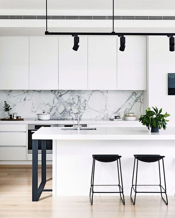 a white kitchen with a white marble backsplash and metal details for a cool look
