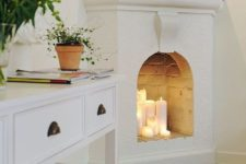 05 a whitewashed non-working fireplace features some candles, which make the space cozier and comfier