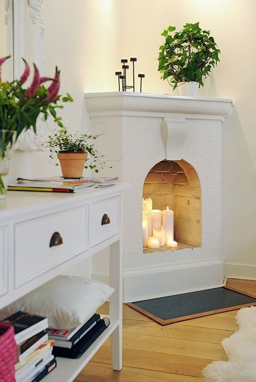 a whitewashed non-working fireplace features some candles, which make the space cozier and comfier