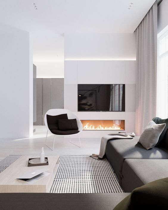 an elegant space with a graphite grey sofa, a built-in fireplace and lots of white color