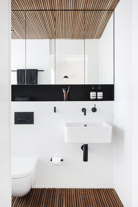 an ultra-modern space with small white tiles, black fixtures and a built-in shelf