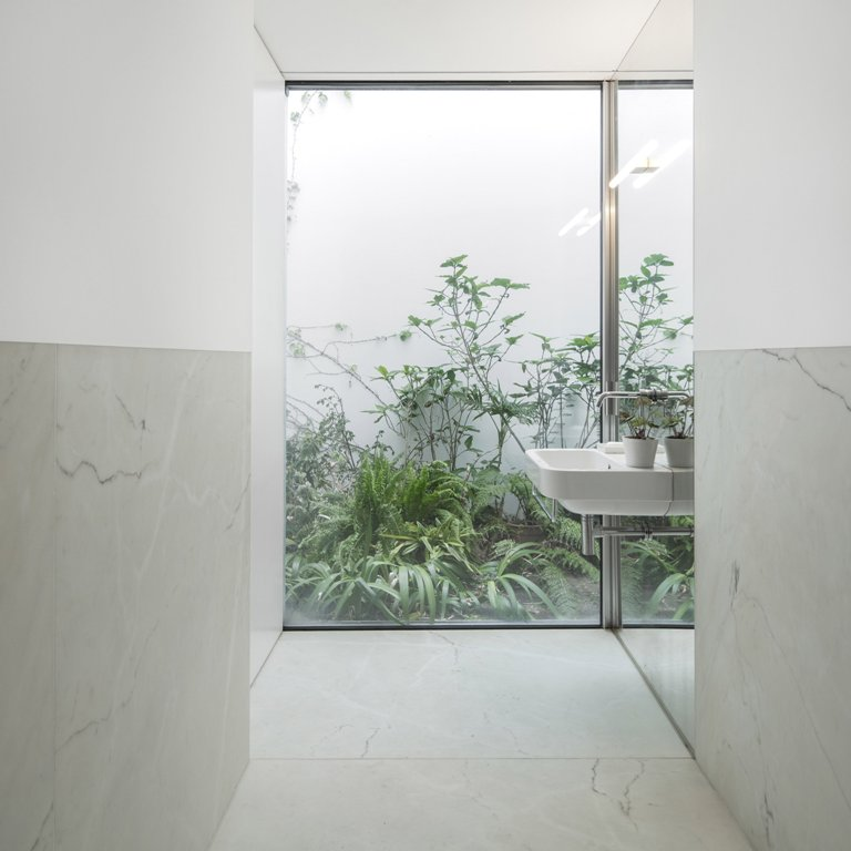 The bathroom is with a view to outdoors, and a tall wall protects the owners from unwanted eyes