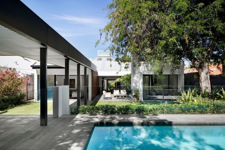 The interior spaces are connected to a garden and to a pool framed by a deck