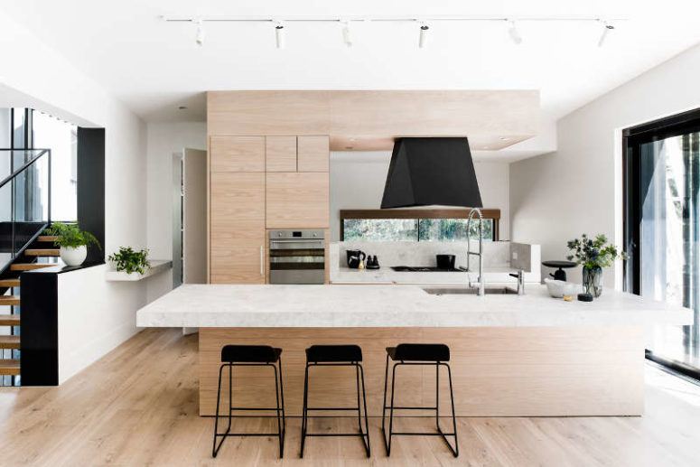 The kitchen is done with light-colored wooden cabinets, some marble and black touches