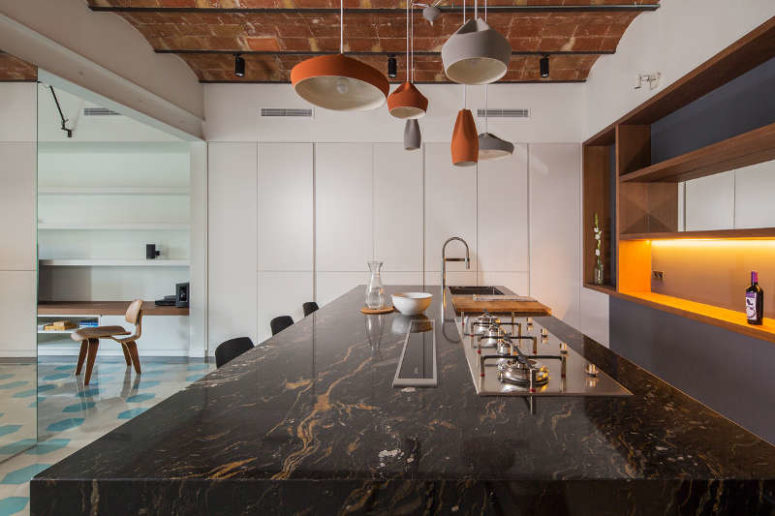 The kitchen island is covered with dark marble and highlighted with eye-catchy porcelain lamps