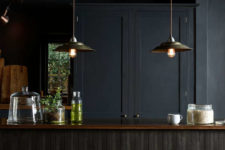 06 The kitchen island with clad with black wooden planks in a very eye-catchy way