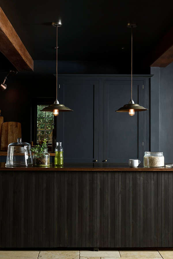 The kitchen island with clad with black wooden planks in a very eye-catchy way