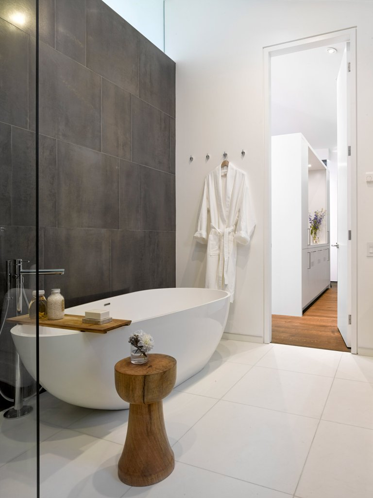 The master bathroom is done in white except for one accent wall clad with graphite grey tiles, and natural wood adds a spa touch