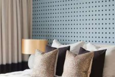 06 The master bedroom is done with a blue pegboard wall, a large bed and metallic shade lamps