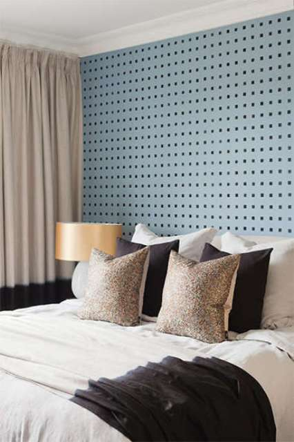 The master bedroom is done with a blue pegboard wall, a large bed and metallic shade lamps