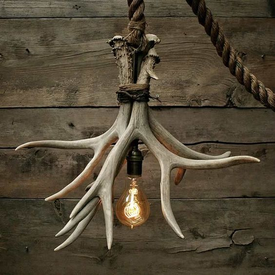 a cabin-inspired chandelier made rope, antlers and a bulb for a bold rustic touch