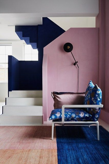 a gorgeous sculptural entryway with a dusty pink wall and navy and white staircase