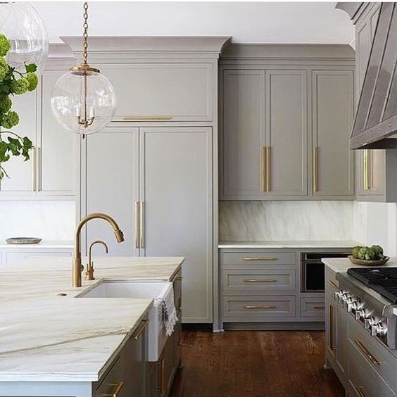 a vintage light grey kitchen with brass touches and antique-styles fixtures looks elegant