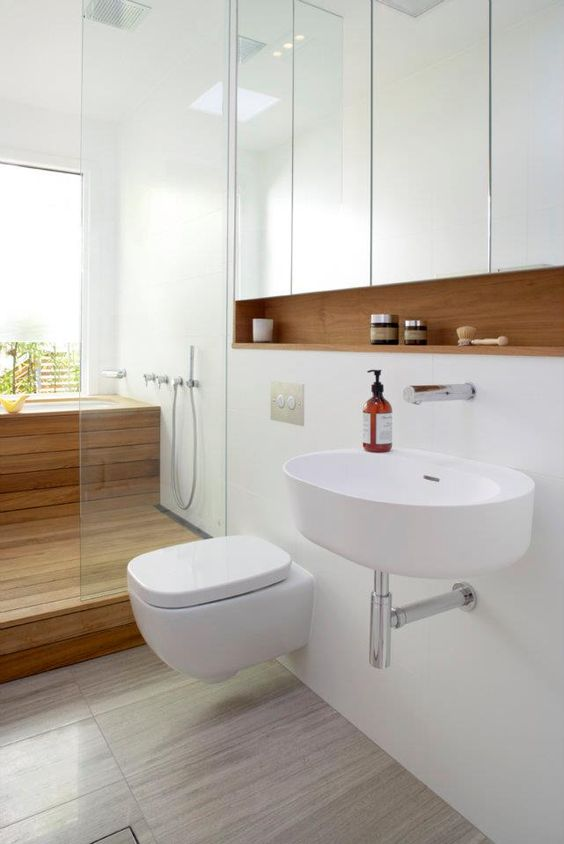 a white space with a wooden built-in shelf, a wood clad shower and bathtub and sleek white panels