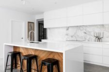 an all-white kitchen with a marble backsplash and a white kitchen island clad with wood