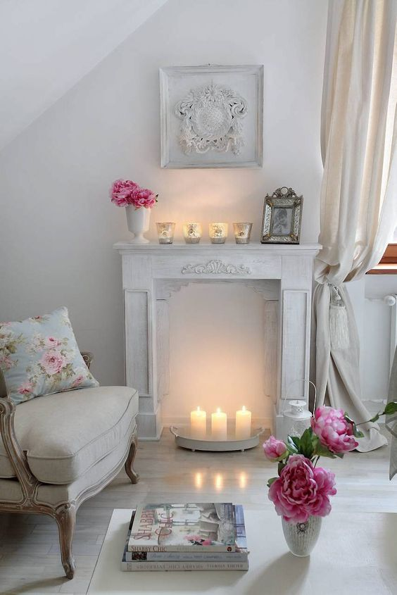 warm up your space with a faux fireplace with candles inside it and on it