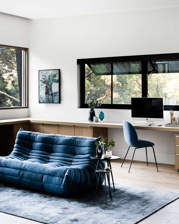 The home office is done with a long windowsill desk, a blue chair and a matching sofa