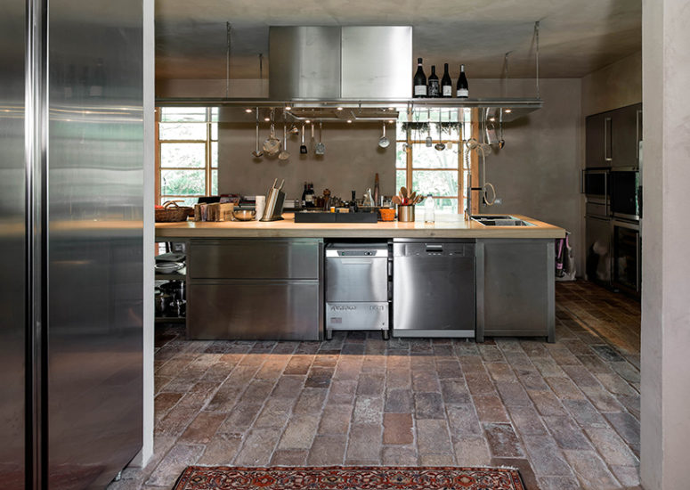 The kitchen is stainless steel, with concrete and brick floors, which altogether create a cool industrial feel