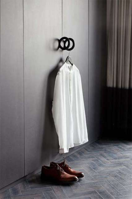 The wardrobe is sleek and dark, with round handles, which can be used for haanging clothes