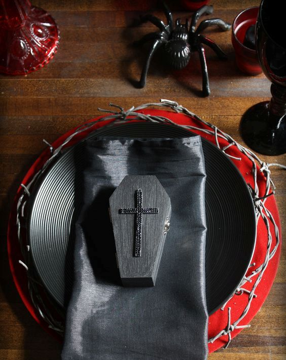 a black and red tablescape with spiders, coffins and textured plates for a vampire party