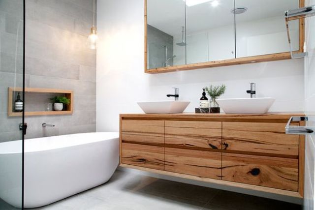 a modern space with a grey tile wall, a wooden vanity and white sinks and a bathtub