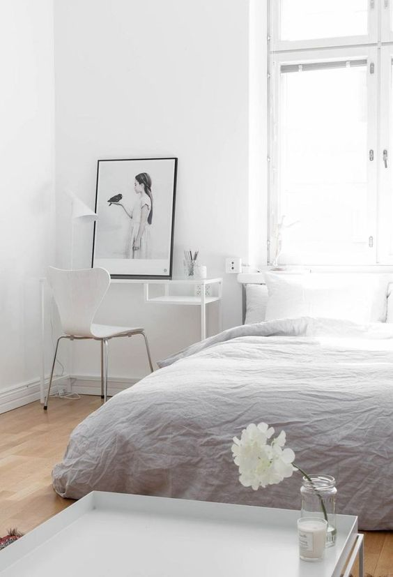 an airy neutral bedroom with a working space in the corner that may double as a makeup nook