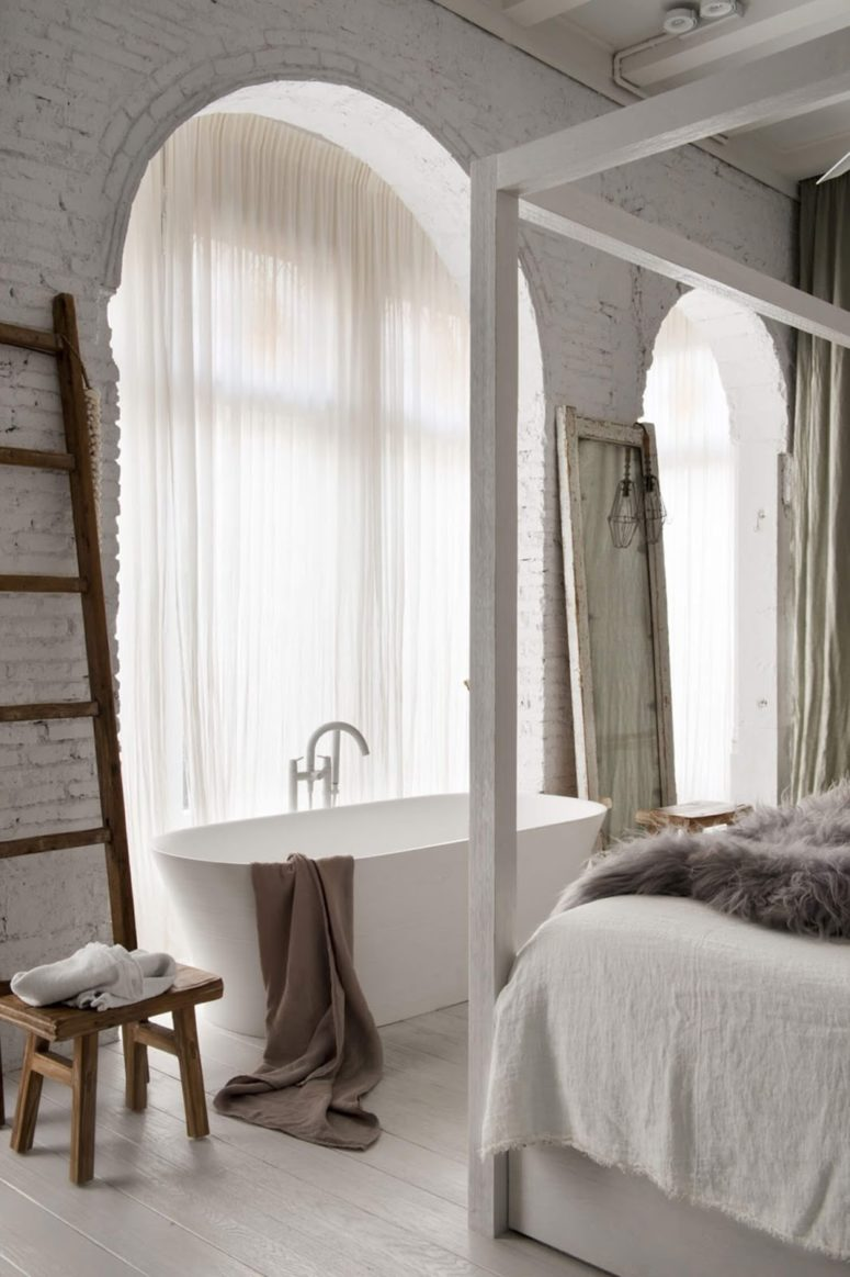 Big arched windows bring much light in, and a bathtub looks chic and gorgeous
