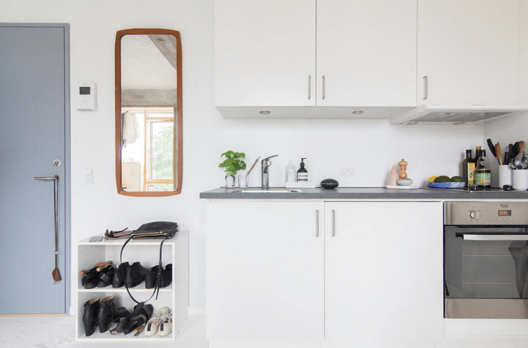 The kitchen is all-white, with grey countertops and it's located at the entrance