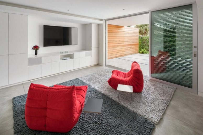 This space with a TV and red chairs is located next to a terrace, which is also kept private with screens