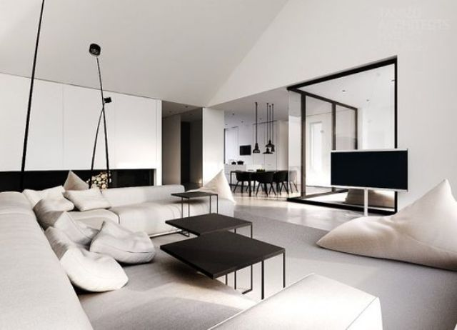 a chic neutral space with a black fireplace and tables and glazed walls to connect with other spaces