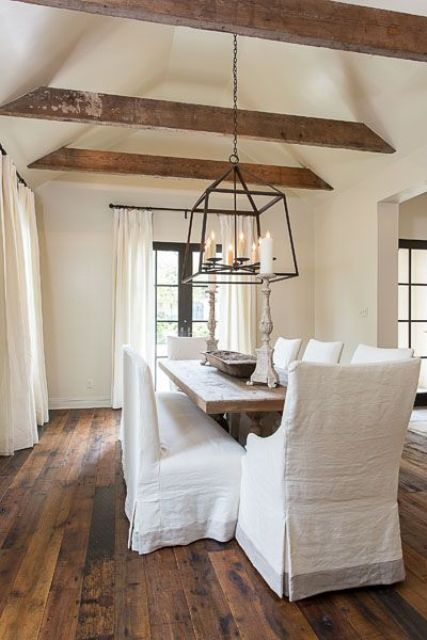 a shabby chic dining room features a vaulted ceiling with exposed wooden beams