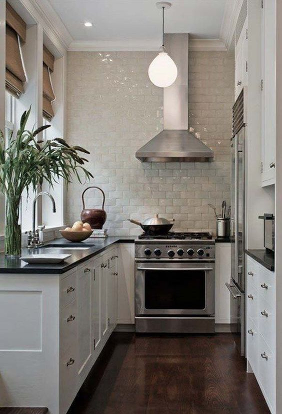 a small U shaped kitchen with a cooker and hood in the center