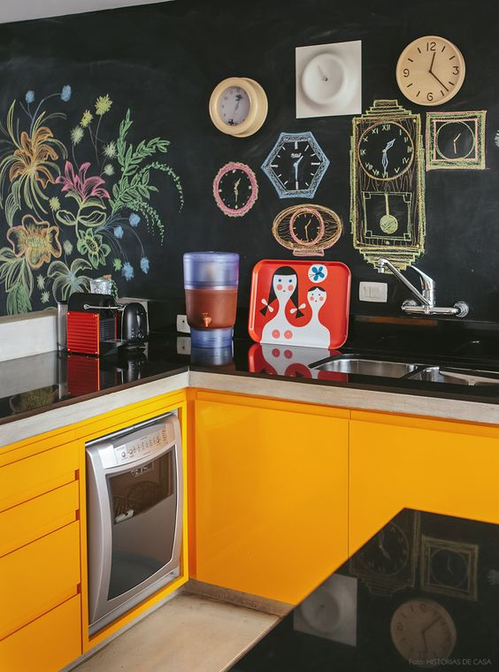 orange kitchen cabinets with sleek black countertops and chalkboard walls for a family retreat