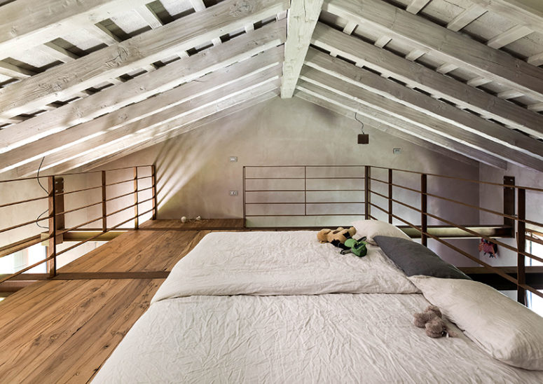 The attic space is used for a bedroom, where you can see only exposed wooden beams and two beds - what else do we need for a cozy nap