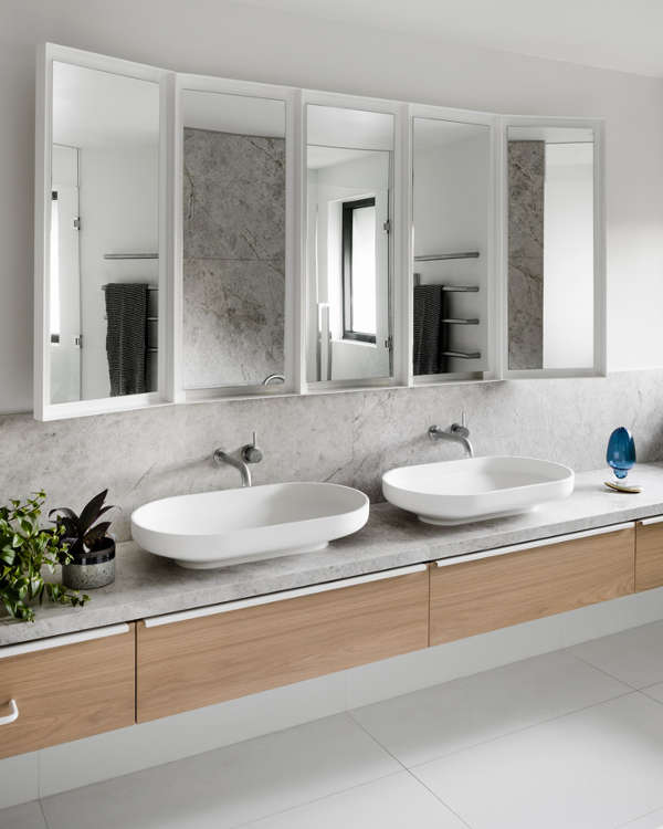 The large master bathroom is done with grey concrete, a large mirror, vanity and two sinks