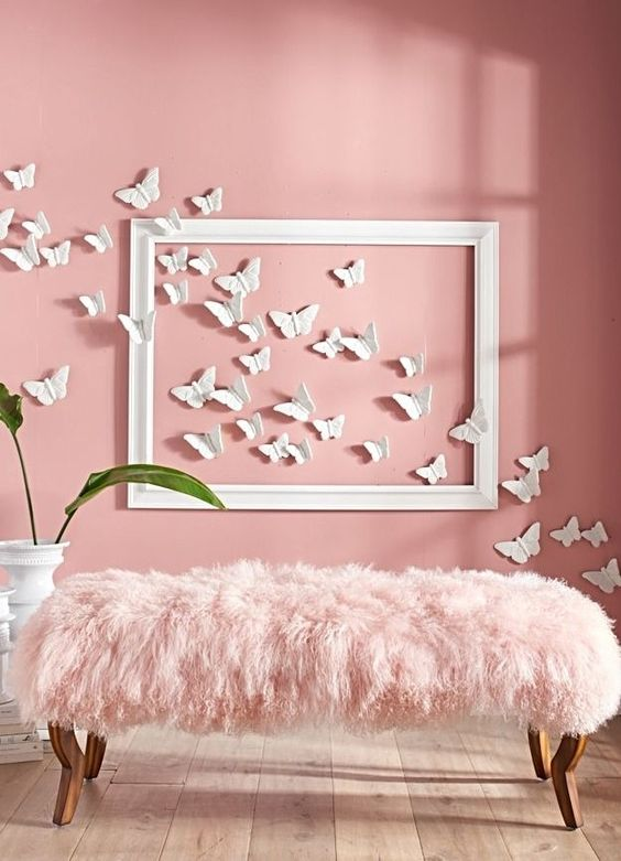 a hot pink wall with butterflies and a pink fur bench look chic together