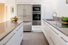 09 a modern white kitchen with stainless steel counters, handles and appliances