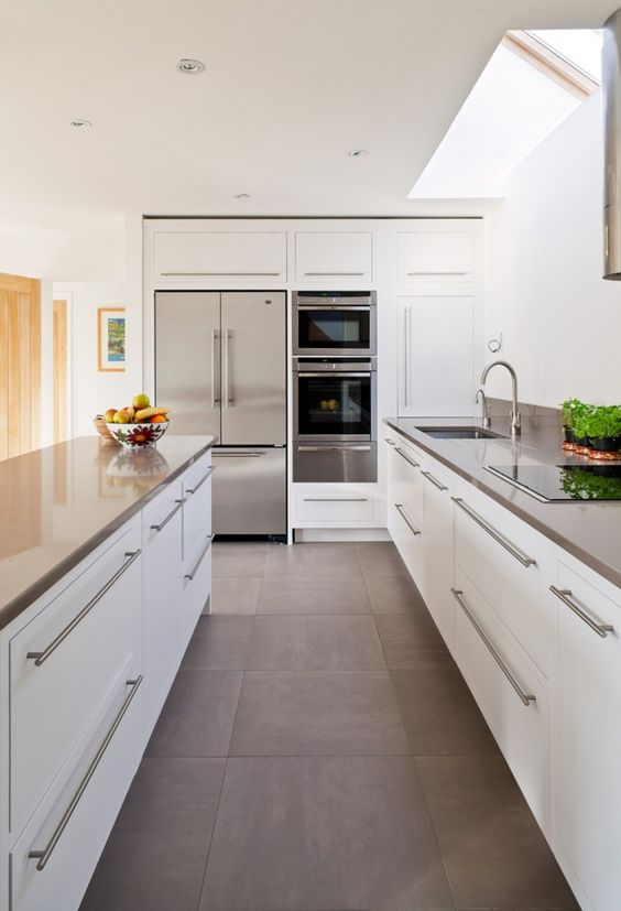 a modern white kitchen with stainless steel counters, handles and appliances