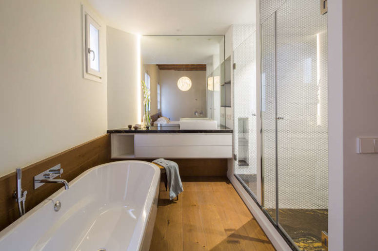 The shower is double, and there's a vanity with a mirror, a large bathtub looks very welcoming