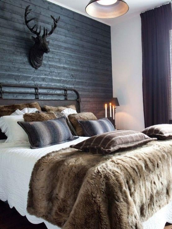 a rustic bedroom with faux fur pillows and a throw blanket, which will keep u warm while sleeping