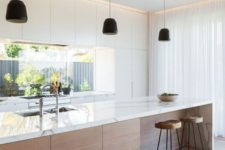 11 a modern light-colored kitchen with a wooden kitchen island and marble counters