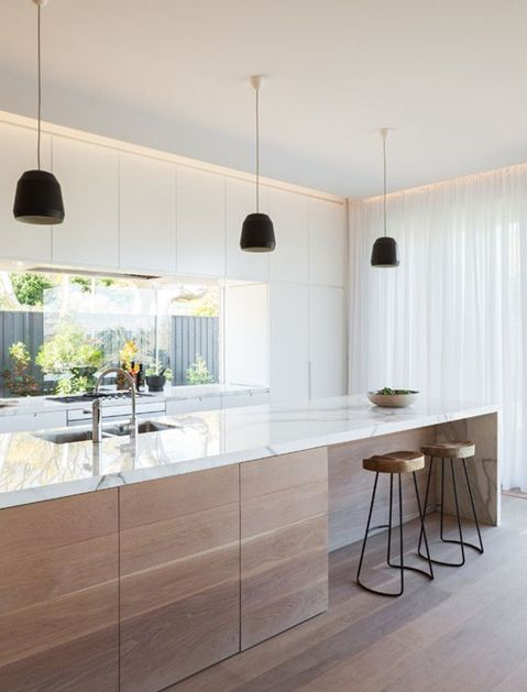a modern light-colored kitchen with a wooden kitchen island and marble counters