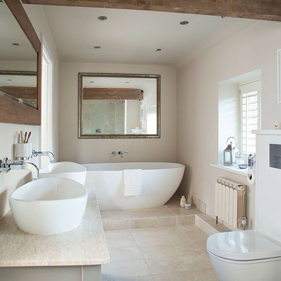 a modern soft-colored bathroom with a free-standing tub, white sinks and neutral tiles