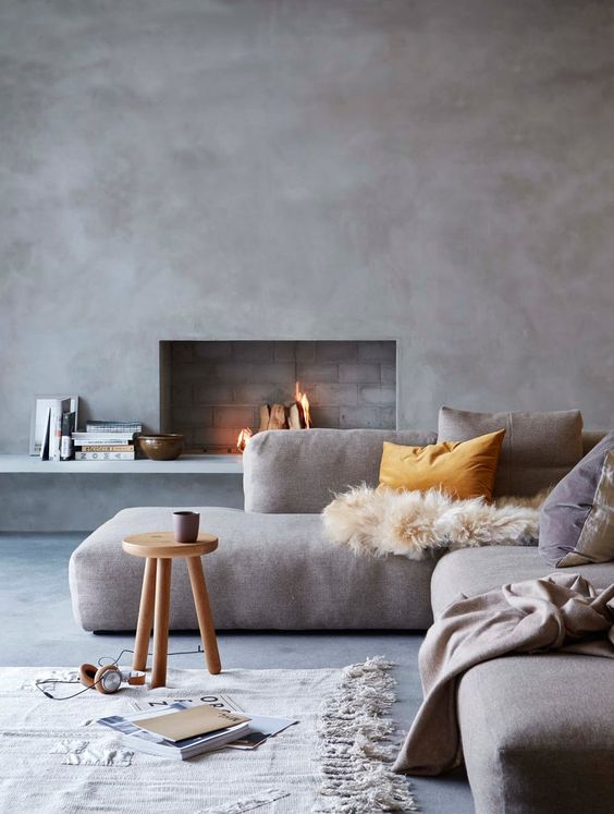 a modern space with concrete walls, a working fireplace, comfy upholstered sofa and textiles