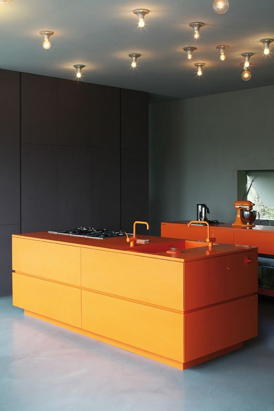 a moody kitchen with a bold orange kitchen island and cooking space to cheer it up