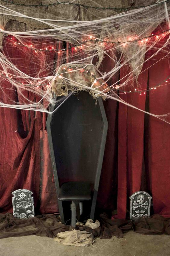 an old open coffin, some cobwebs, red string lights and dollar store tomb stones surrounded by brown tulle