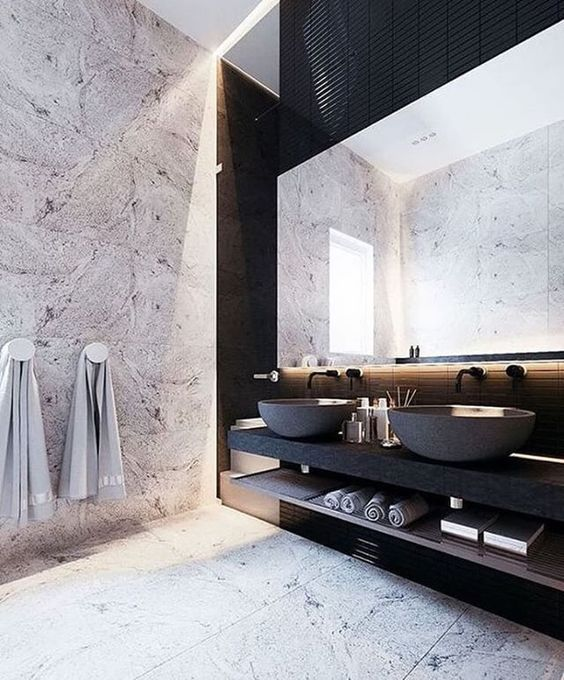 a stone wall, marble tiles and a matte black vanity and concrete sinks